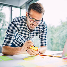 A business man writing down sticky notes on a desk