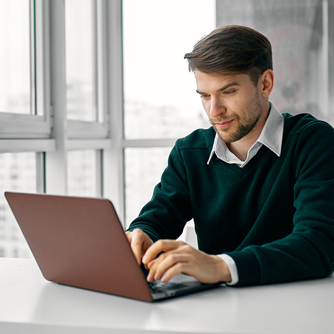 A man sitting by a window in a highrise building typing on a laptop.