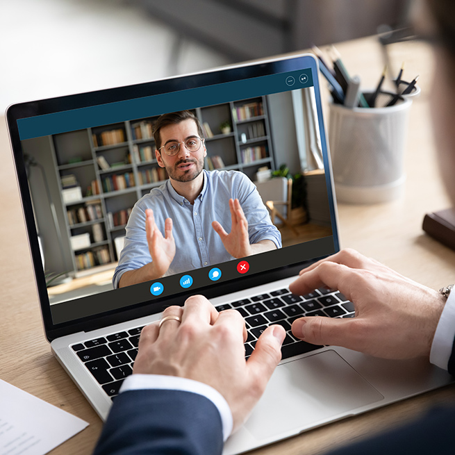 Two people video chatting with one on the screen of a laptop and the other facing the screen.