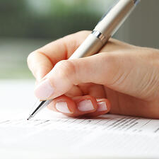 A close up shot of a hand filling out a form.