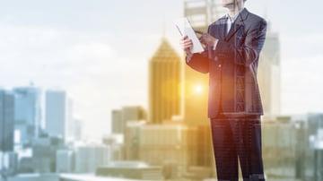A city backdrop overlaid with a man on an ipad