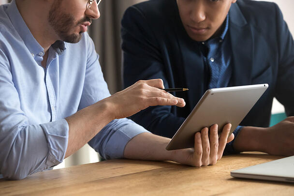 Two men discussing information on an iPad