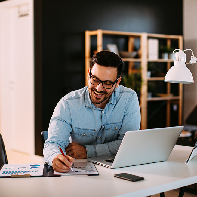 Man in home office writing down notes