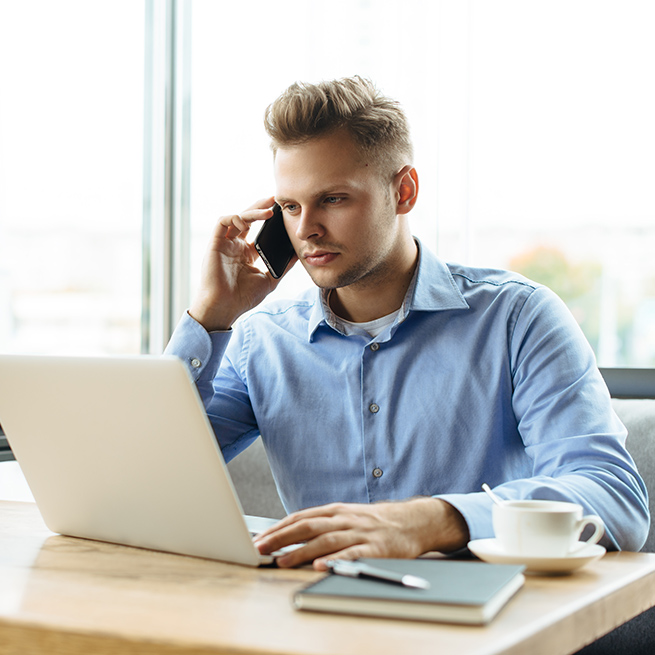 Person on phone in front of laptop